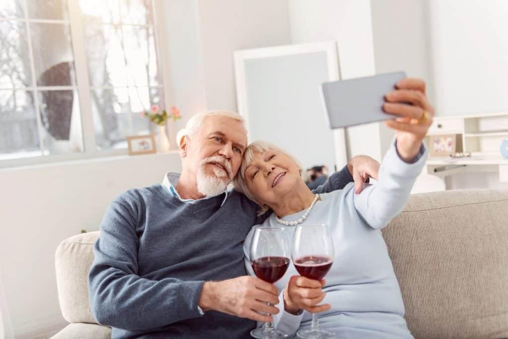 זוג עם שיער אפור שותים ומצלמים סלפי