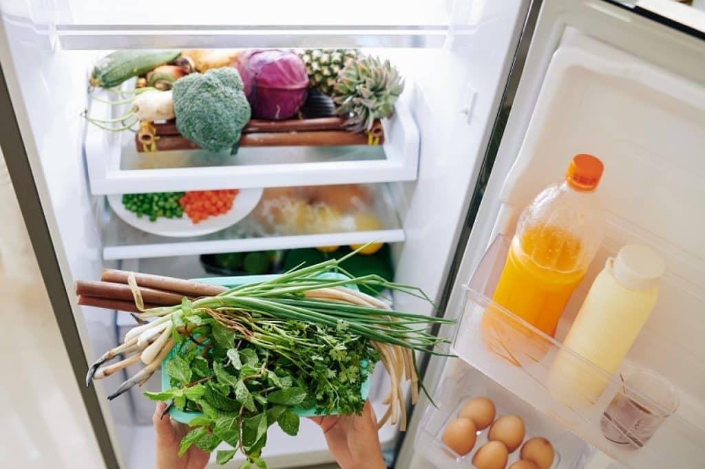 ידיים של אישה מוציאה ירקות כדי להכין ארוחת ערב בריאה