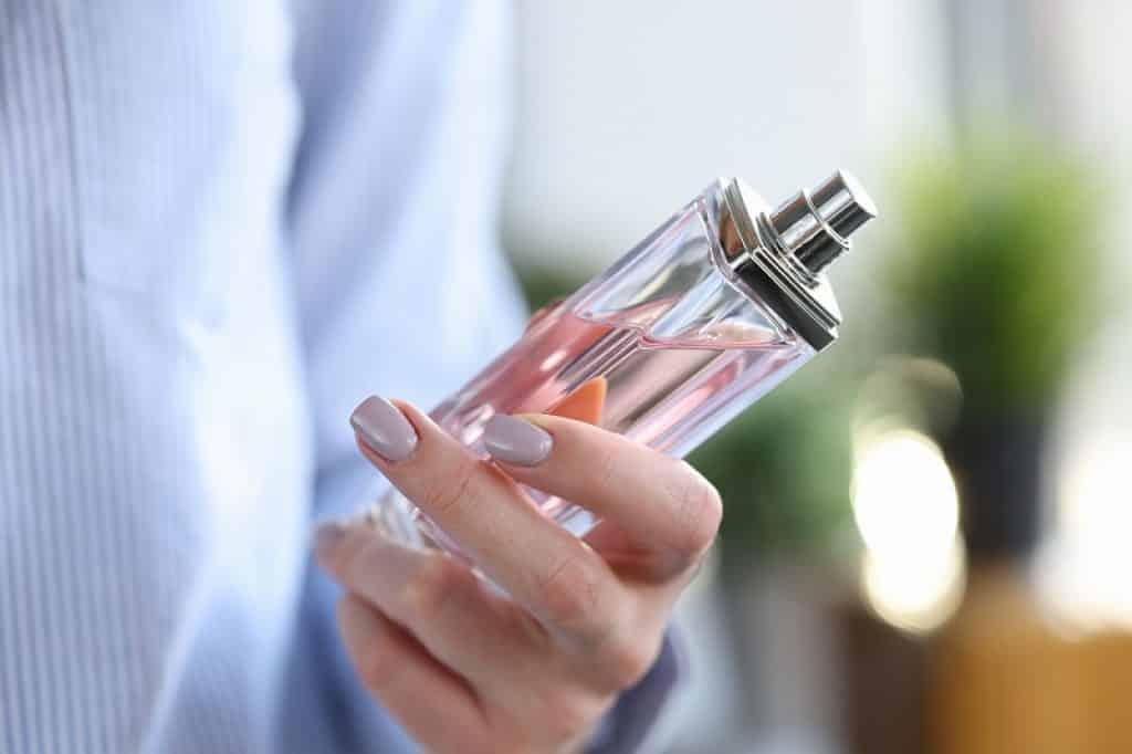 יד מחזיקה בקבוק ורוד של בושם לאישה