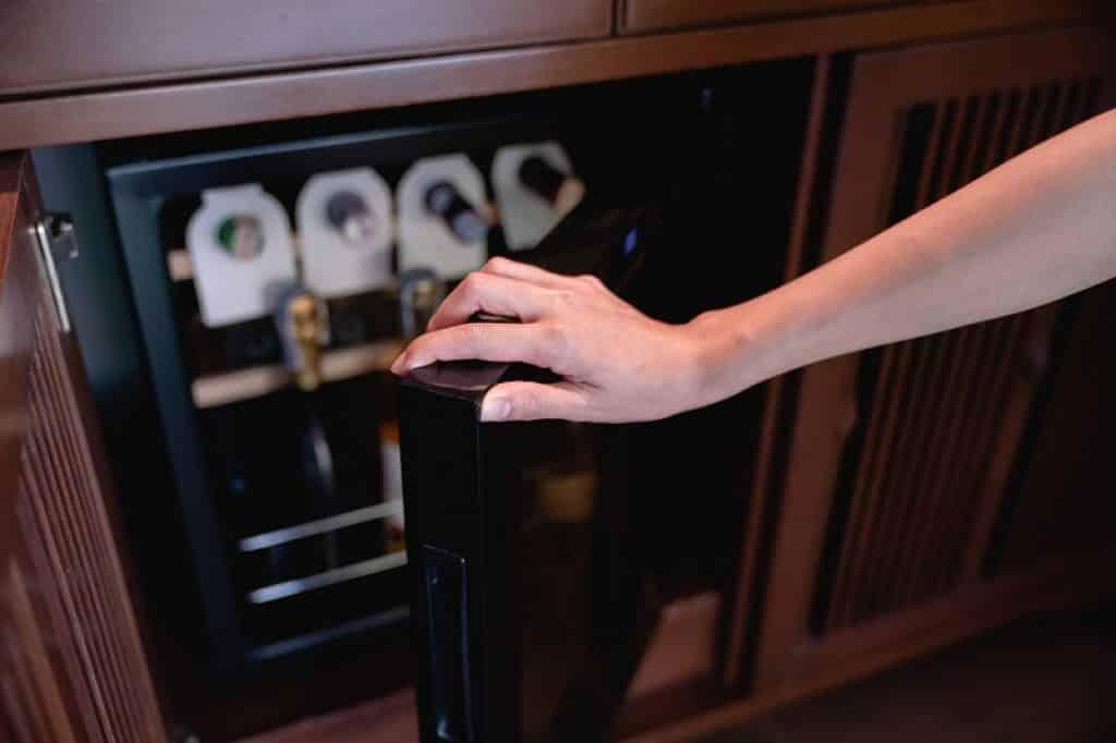 יד של אישה מוציאה יין מתוך מקר משרדי קטן