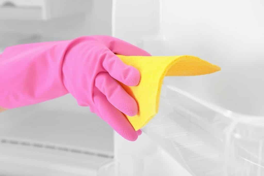 יד של אישה עם כפפה ורודה מנקה עם סמרטוט צהוב