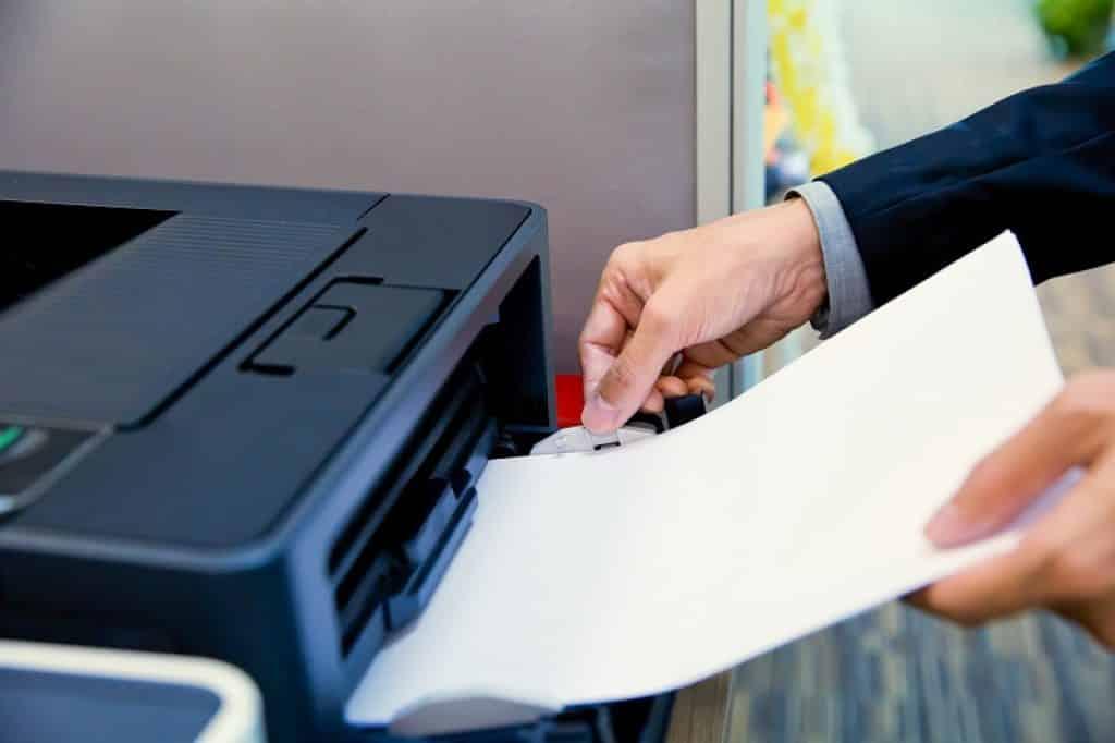 יד של איש בחליפה מחזיקה ערימת דפים ליד מדפסת HP
