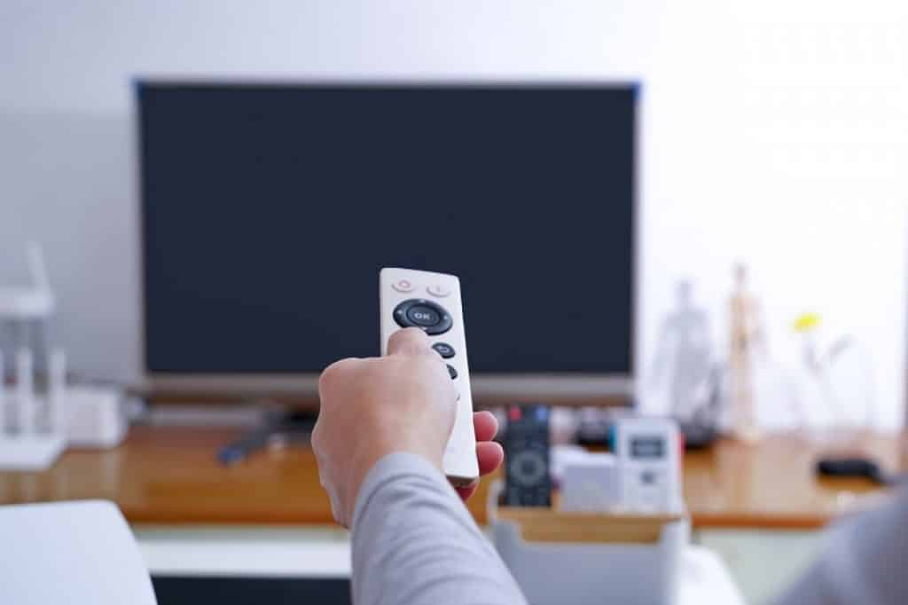 יד של גבר עם שלט לבן מול טלוויזיה כבויה בסלון