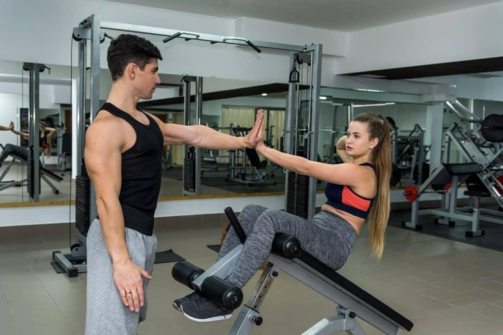 מתאמנת עושה תרגילי בטן על ספסל אימון ונותנת כיף למאמן