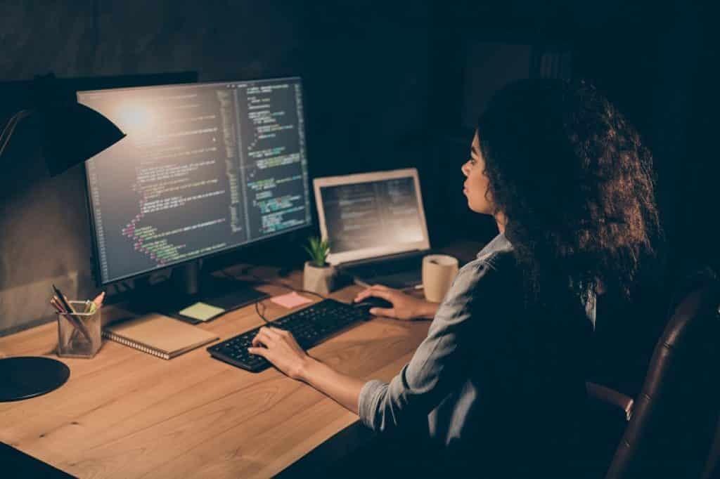 נערה עם תלתלים בצבע שחור עובדת על מחשב נייח