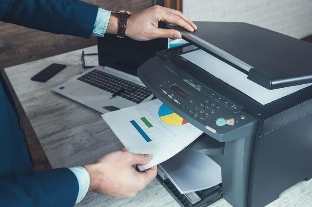 עובד במשרד מצלם דפים עם גרפים צבעוניים