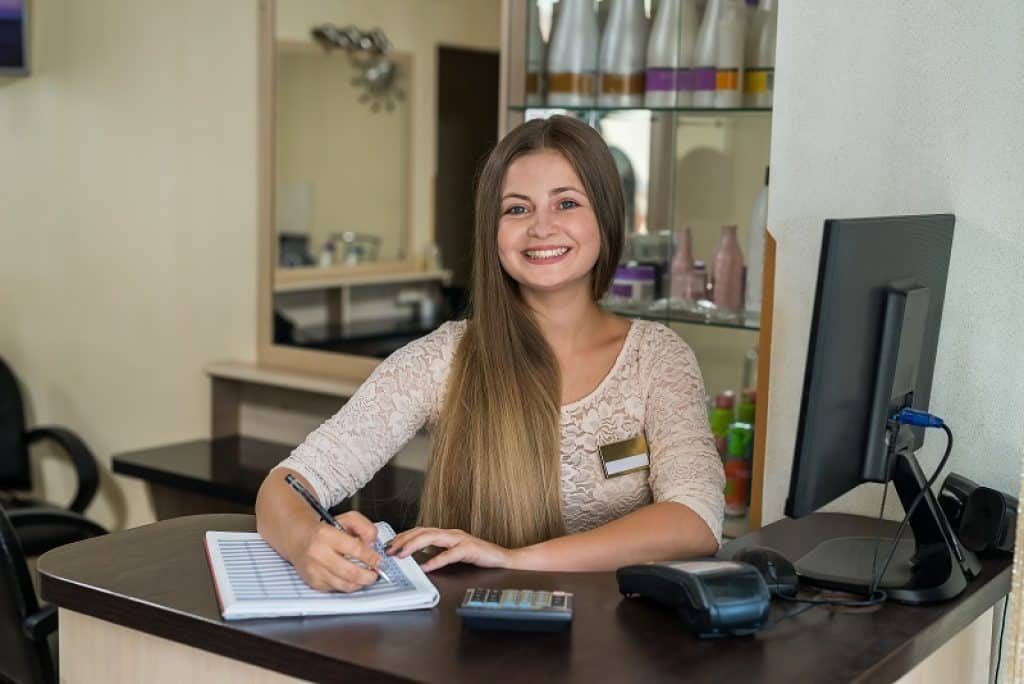 פקידת קבלה עם שיער ארוך מחייכת וכותבת על בלוק דפים