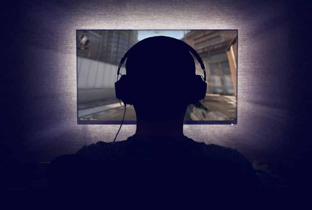 צילום אחורי של בחור צופה במסך מחשב לגיימרים