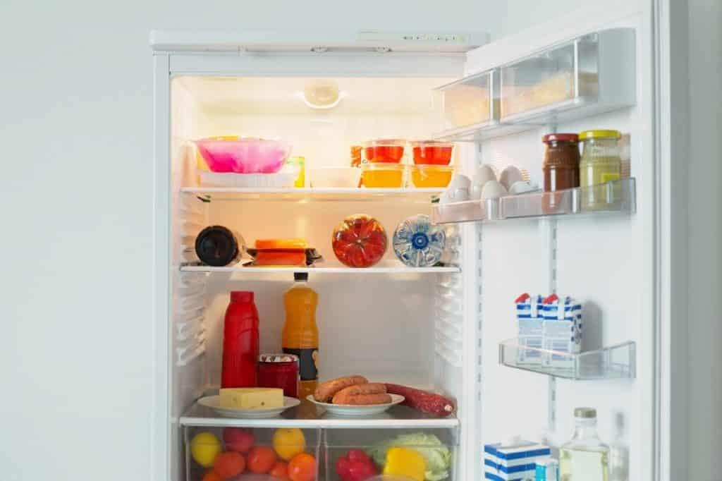 צילום פנימי של מקרר משרדי קטן מלא במוצרי מזון