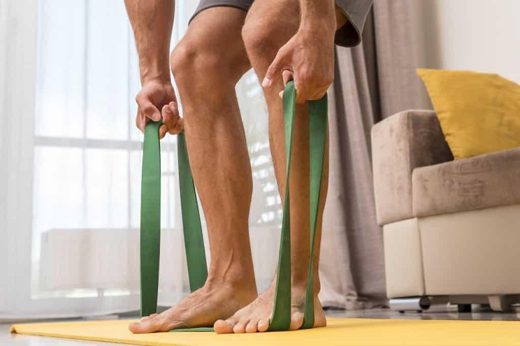 רגליים של גבר דורכות על רצועת אימון ירוקה
