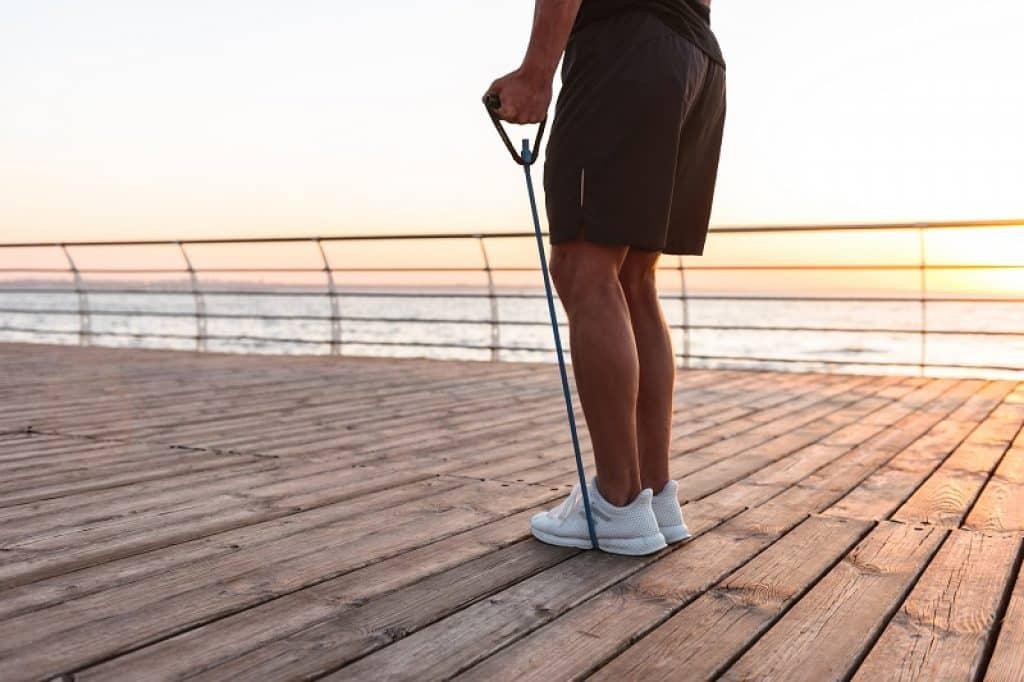 רגליים של גבר עם נעליים לבנות עומדות על דק בשקיעה