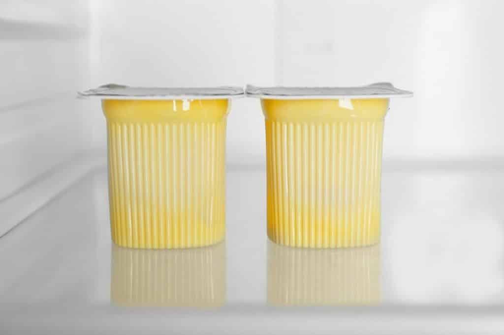 שני מעדנים בגביע עם מכסה לבן צהוב מונחים על מדף