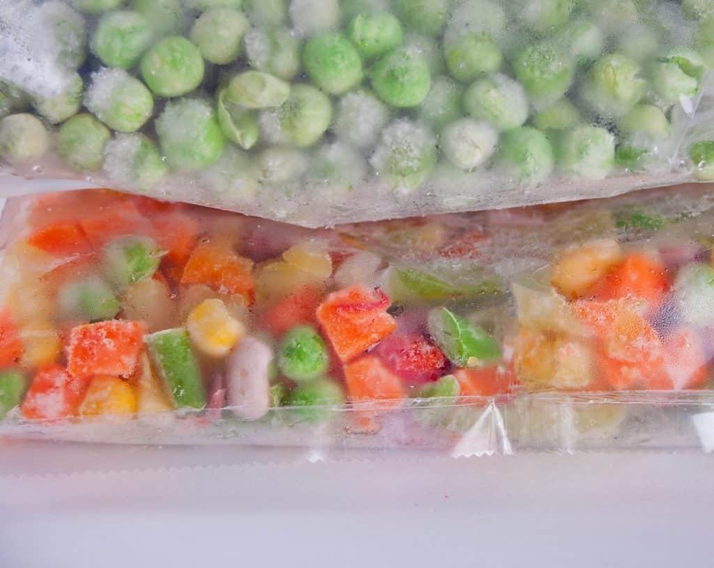 שקית עם לקט ירקות ומעליה מונחת שקית עם אפונה קפואה