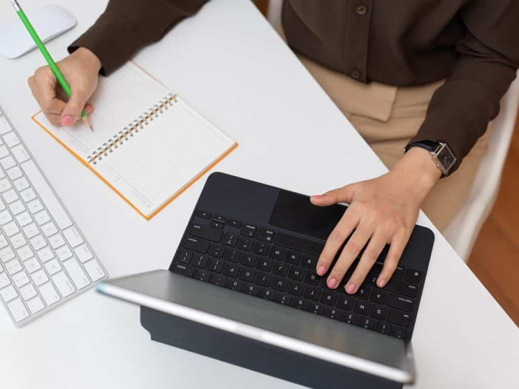 תמונה של יד של גבר כותבת במחברת על שולחן כתיבה