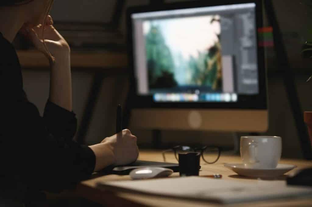 אישה יושבת במשרד ומחזיקה עט אלקטרונית ועורכת תמונה במחשב