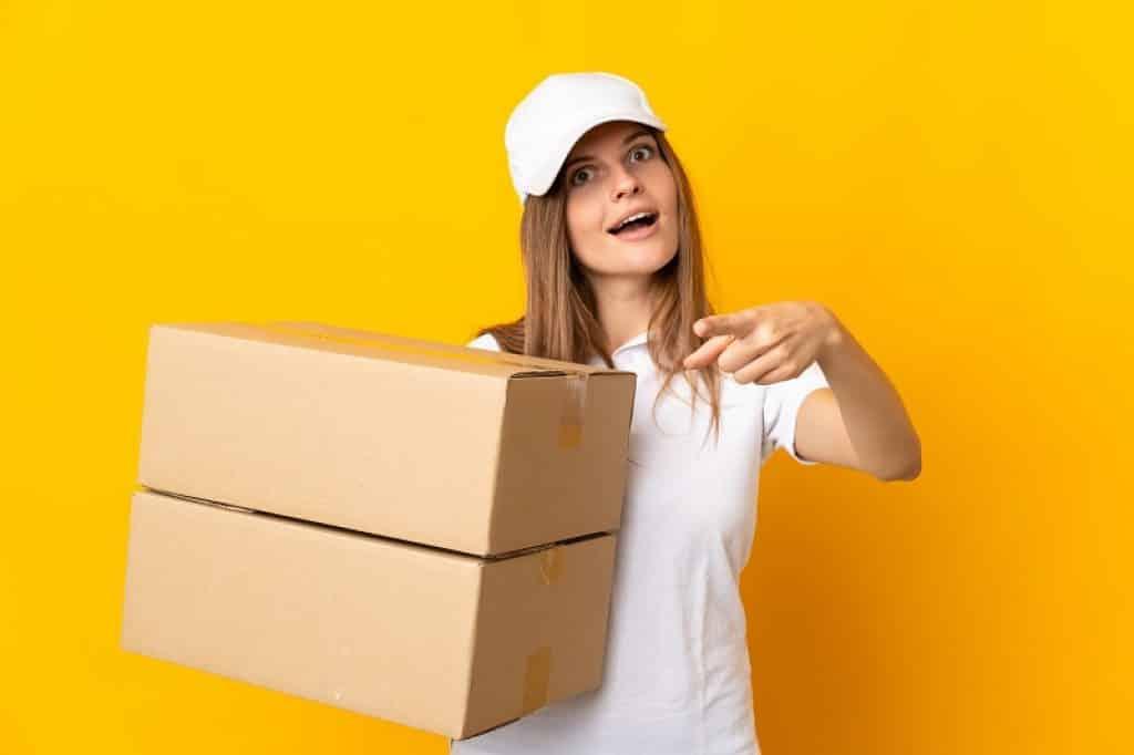 אישה עם חולצה וכובע לבנים מצולמת על רקע צהוב