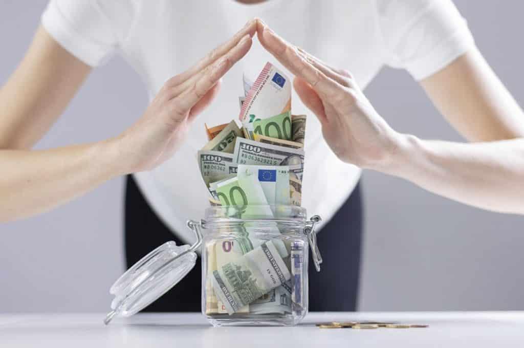 אישה עם חולצה לבנה עומדת ליד צנצנת מלאה בשטרות כסף