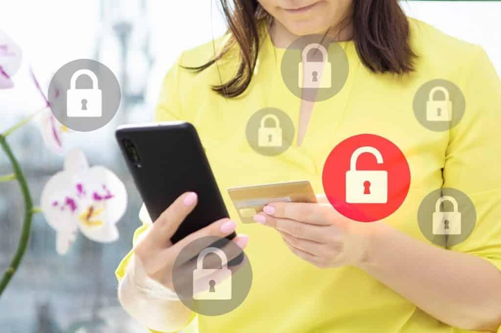 אישה עם חולצה צהובה מחזיקה טלפון וכרטיס אשראי
