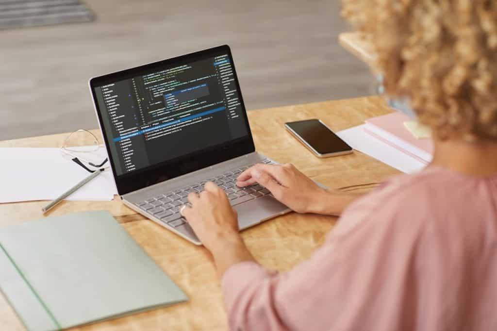 אישה עם תלתלים וחולצה ורודה עובדת על אוטומציה ובדיקת תוכנה