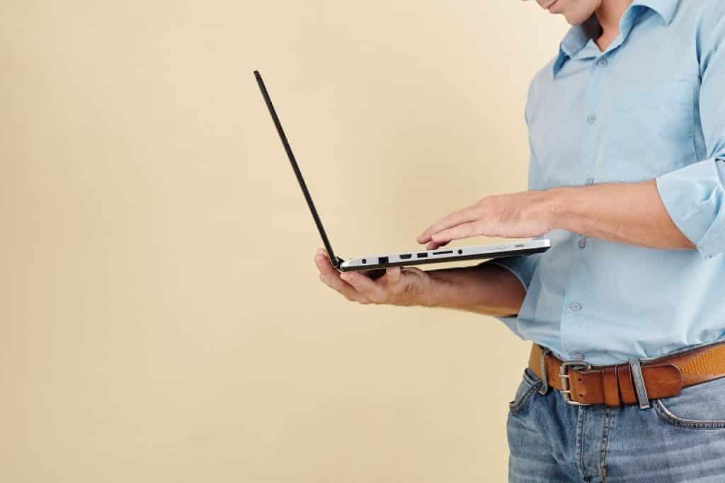 איש עם ג'ינס כחול וחולצה מכופתרת עומד ומחזיק מחשב