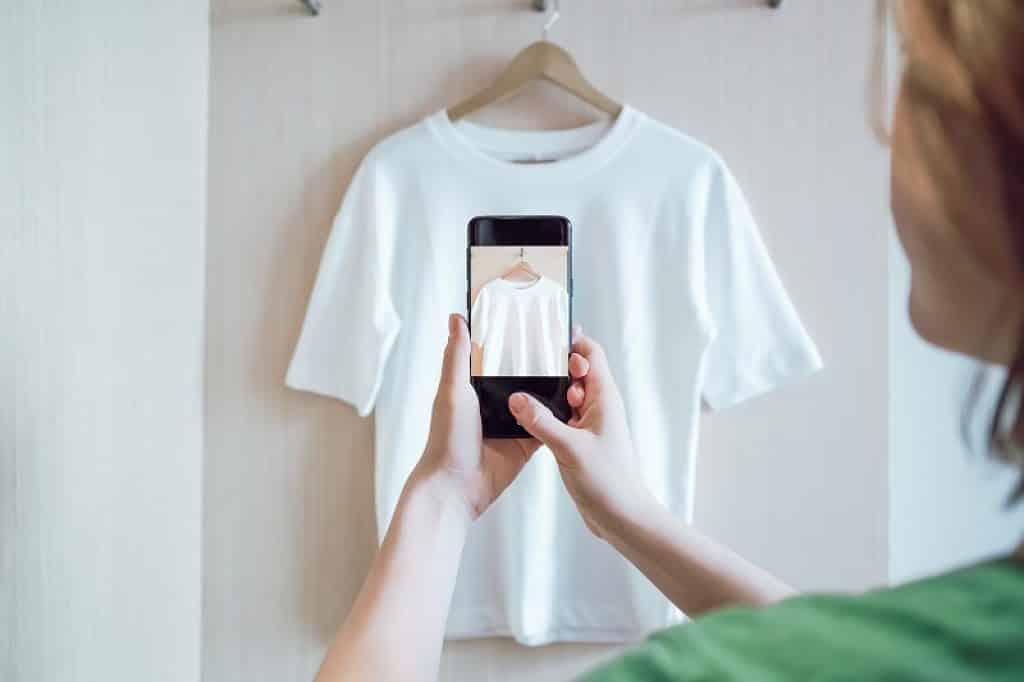 בחורה מצלמת חולצת טי שרט לבנה כדי למכור אונליין