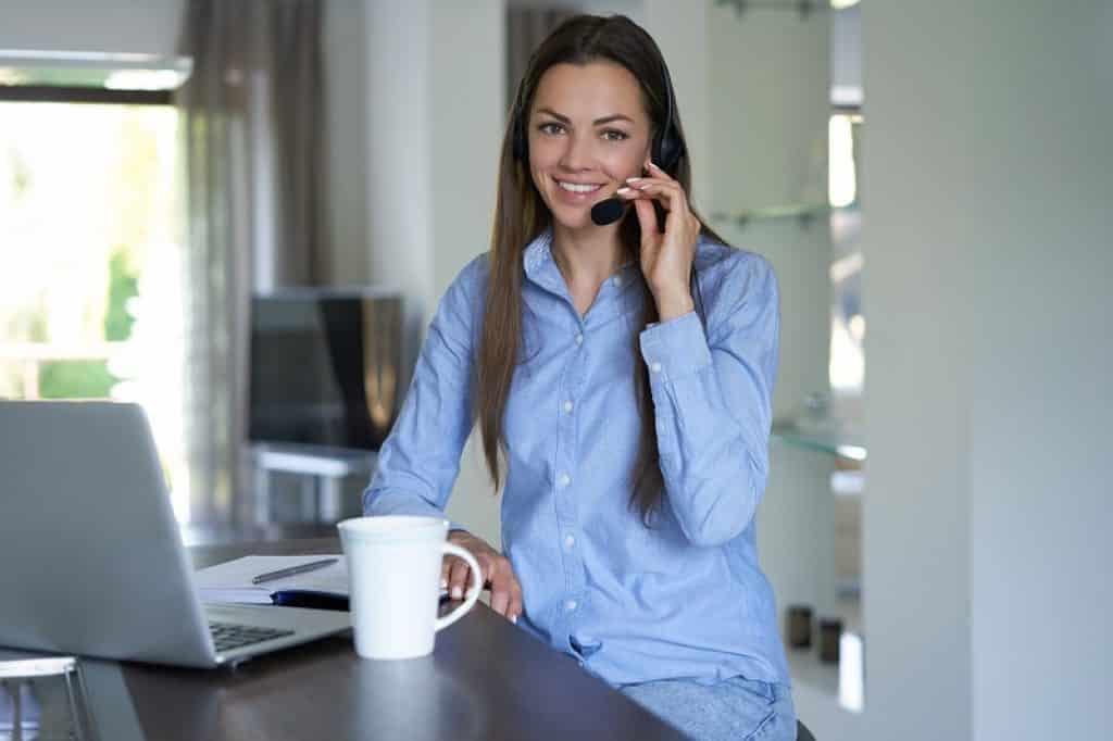 בחורה עם חולצה מכופתרת ואוזנייה עובדת כעוזרת אישית מהבית
