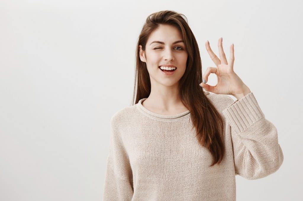 בחורה עם סוודר לבן עושה סימון עם היד