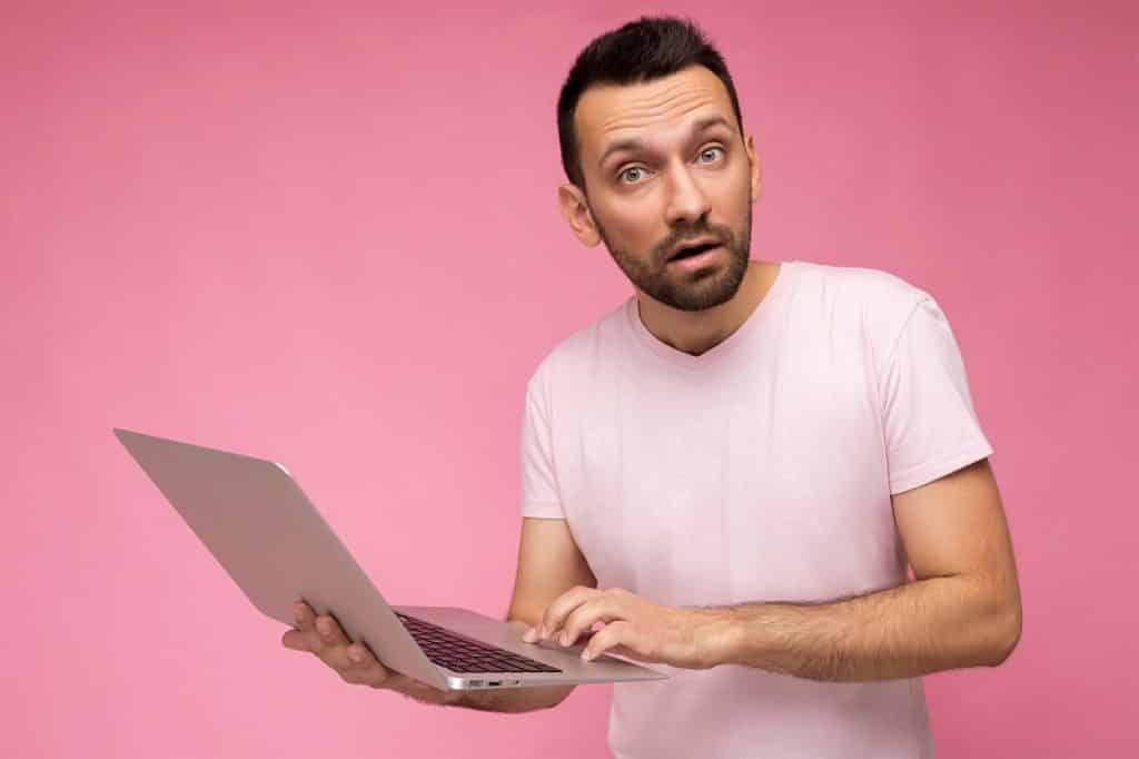 בחור על רקע ורוד מחזיק מחשב נייד בהבעת שאלה