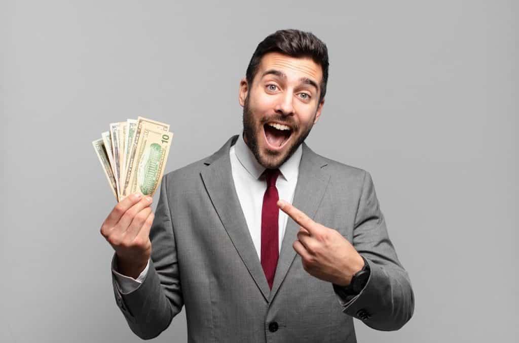 בחור עם ג'קט אפור מחזיק שטרות של כסף ביד