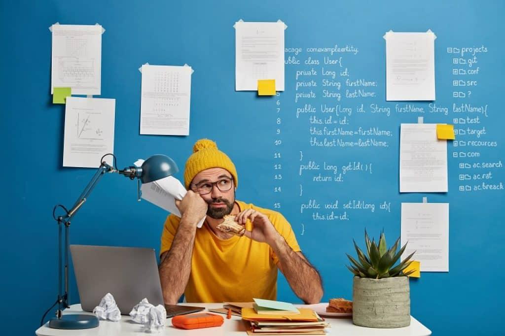 בחור עם חולצה וכובע צהובים במבט שואל שאלה ומיואש
