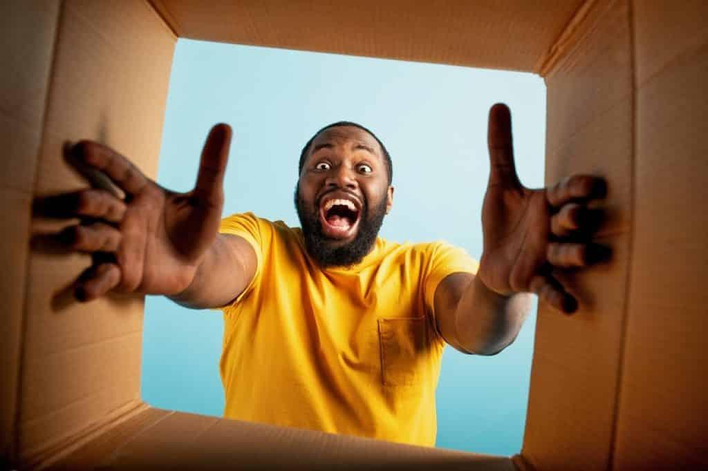 בחור עם חולצה צהובה מחוייך פותח חבילה שהגיעה בדואר
