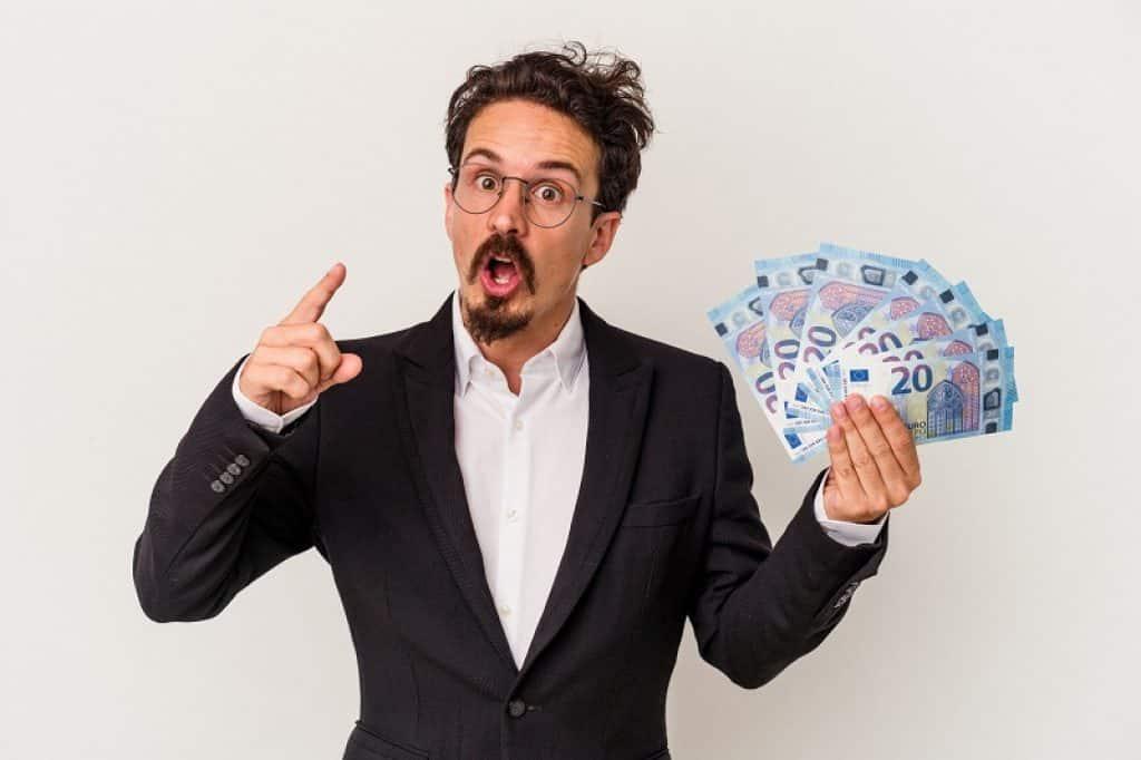 בחור עם משקפיים וחליפה מחזיק כסף במבט של שאלה