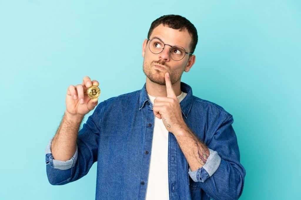 בחור עם משקפיים מחזיק מטבע עם פרצוף של שאלה