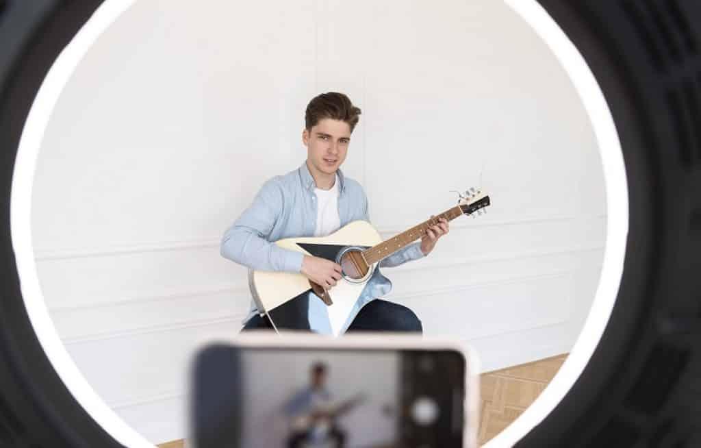 בחור צעיר מצלם את עצמו מעביר שיעור גיטרה ליוטיוב