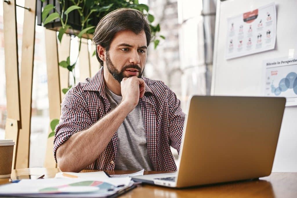 גבר עם זקן עובד על מחשב נייד בבית קפה