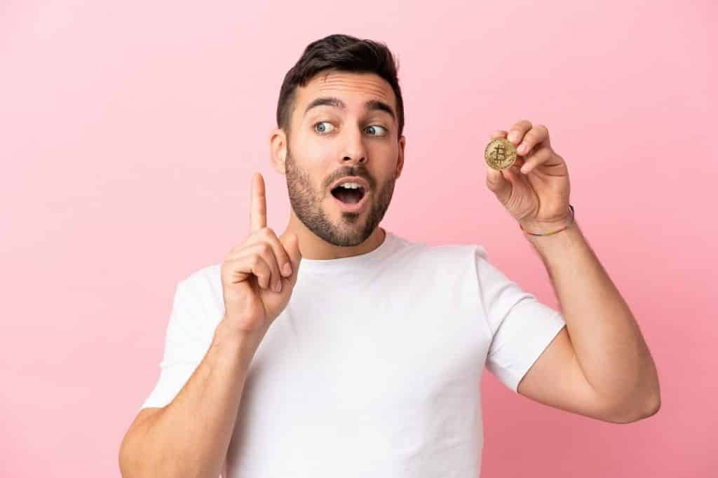 גבר עם חולצה לבנה מחזיק מטבע ומרים אצבע לשאלה
