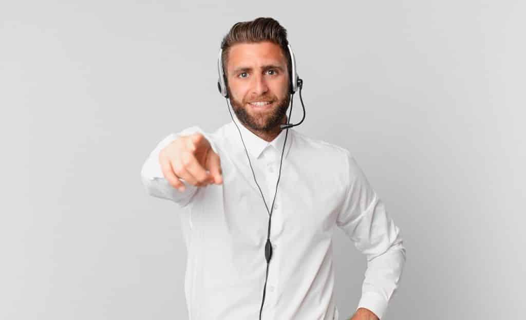 גבר עם חולצה לבנה מכופתרת ואוזניות מצביע לכיוון המצלמה