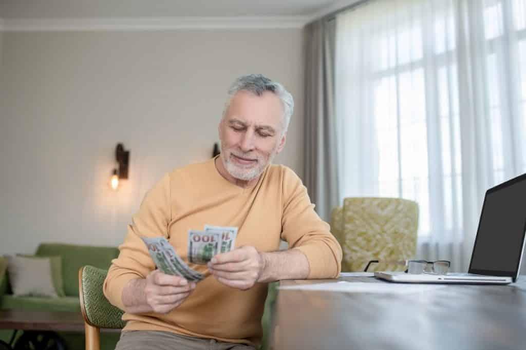 גבר עם חולצה צהובה מחזיק וסופר שטרות של כסף