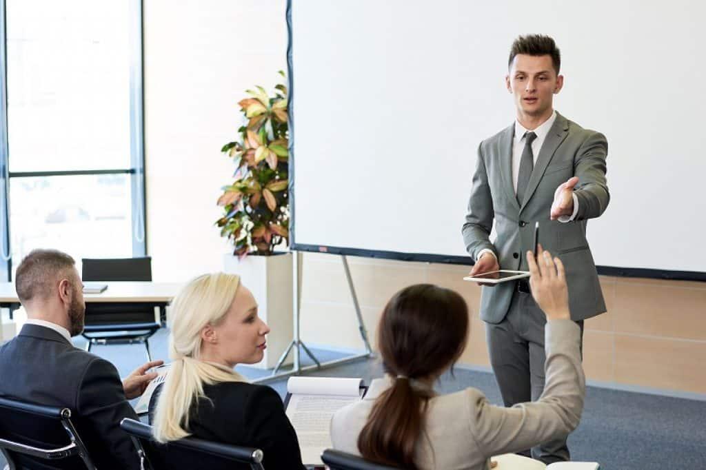 גבר שמעביר הרצאה פונה לאישה שמרימה את היד לשאלה