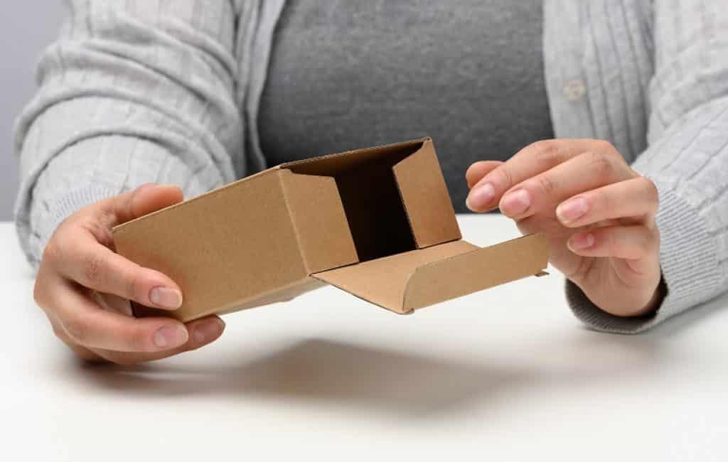 ידיים של אישה עם סוודר אפור מחזיקה פותחת קופסא קטנה