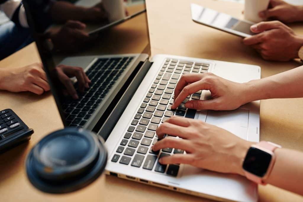 ידיים של בחורה עם שעון חכם שעובדת באוטומציה ובדיקת תוכנה