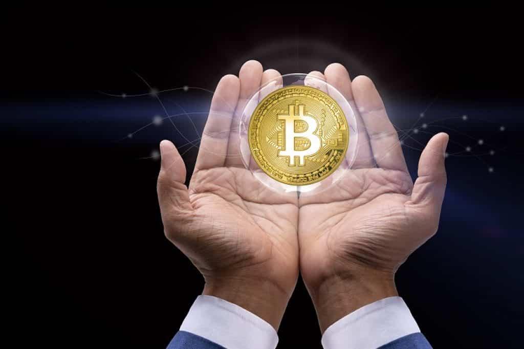 ידיים של גבר מחזיקות מטבע זהב על רקע כהה