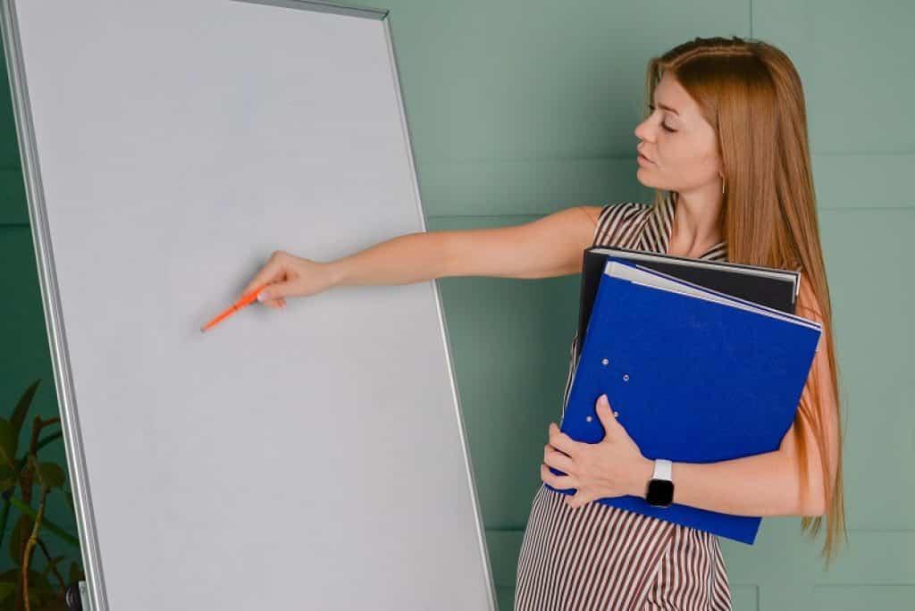 מורה לאנגלית מלמדת מהבית עומדת ליד לוח לבן ומחזיקה קלסרים