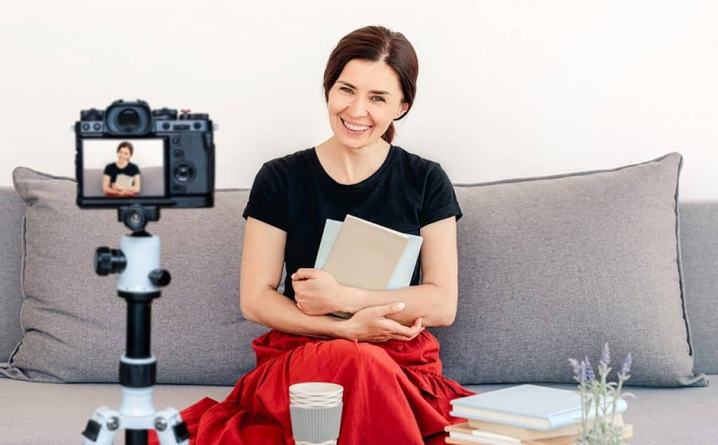 מורה עם חצאית אדומה יושבת על הספה ומעבירה שיעור