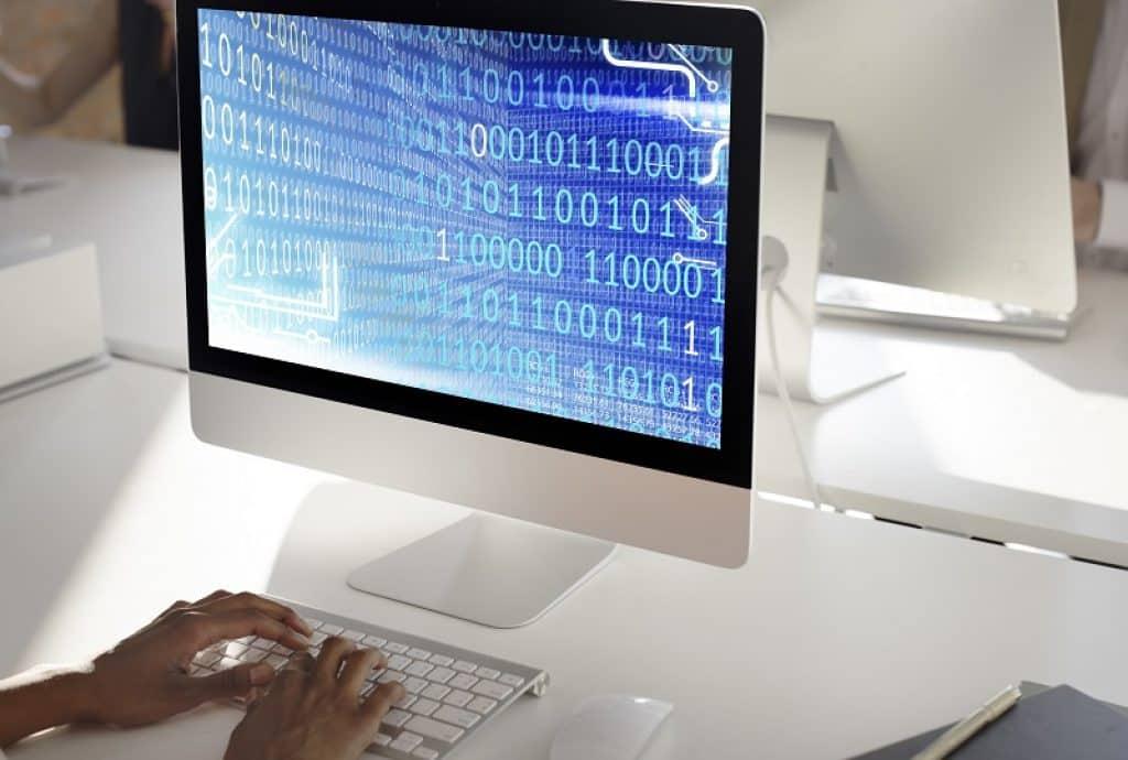 מתכנת יושב על שולחן עם מקלדת לבנה ומקודד