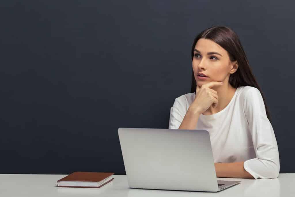 בחורה צעירה עם לפטופ יושבת וחושבת איזה קורס לבחור