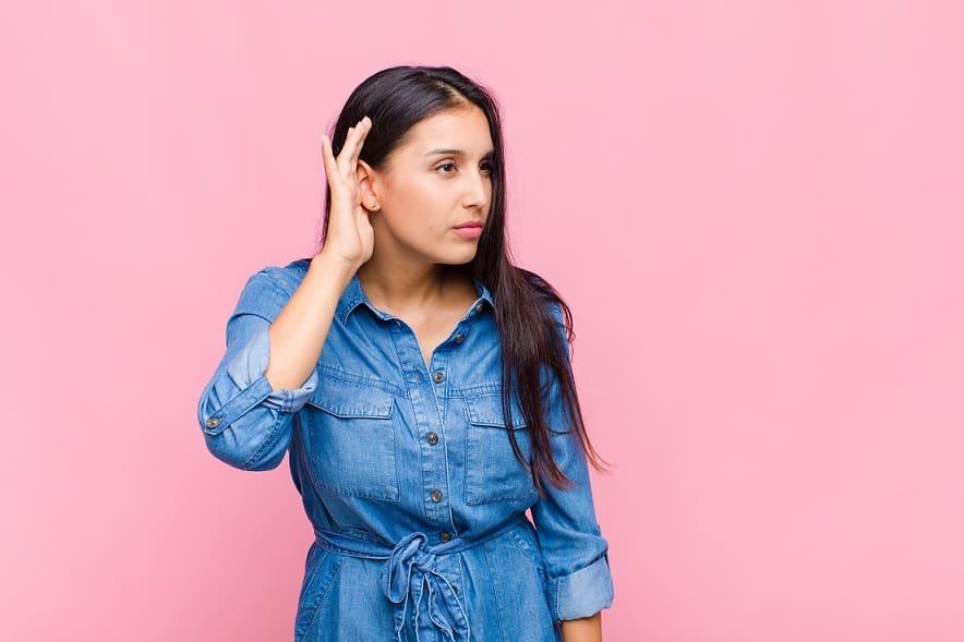בחורה עם אובדן שמיעה עושה תנועה של הקשבה