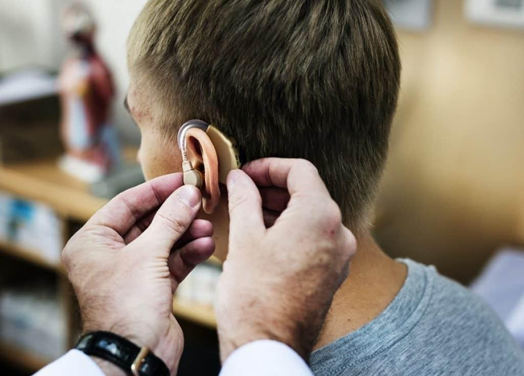 ידיים מרכיבות מכשיר מיוחד לשמיעה על אוזן של גבר