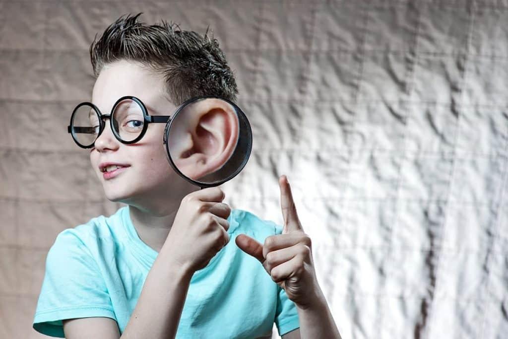 ילד קטן עם משקפיים מחזיק זכוכית מגדלת ליד האוזן שלו