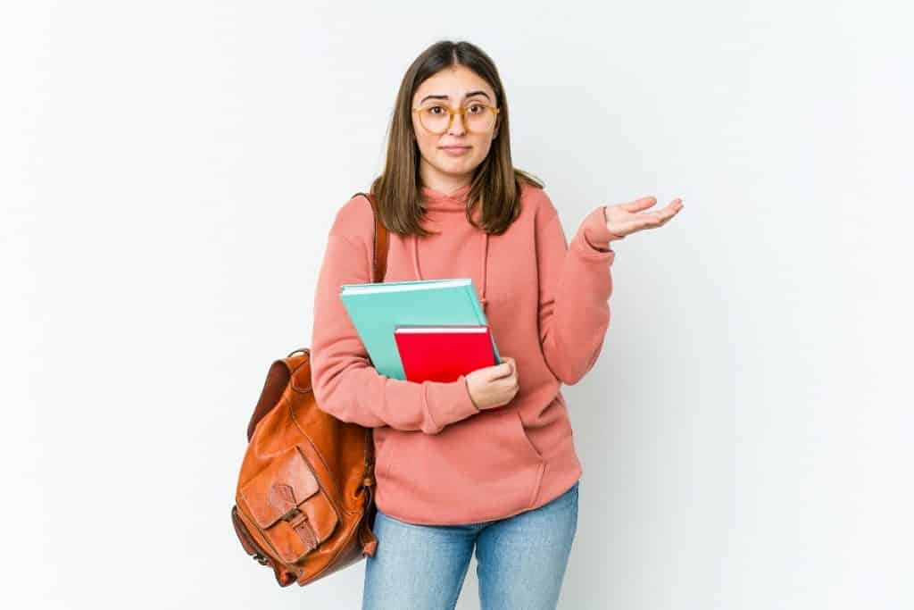 סטודנטית צעירה עם תיק ומחברות שואלת שאלה